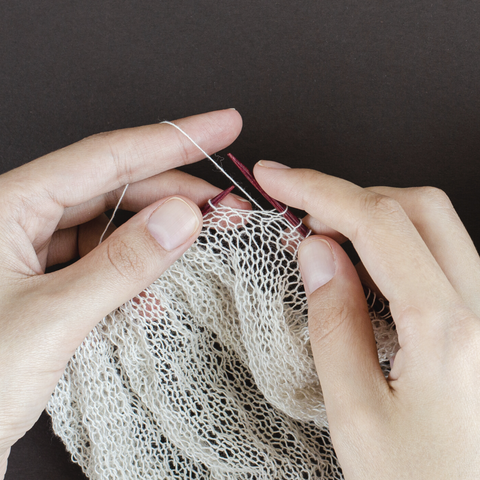 Hands knitting some off white lace weight yarn into a gauzy fabric.