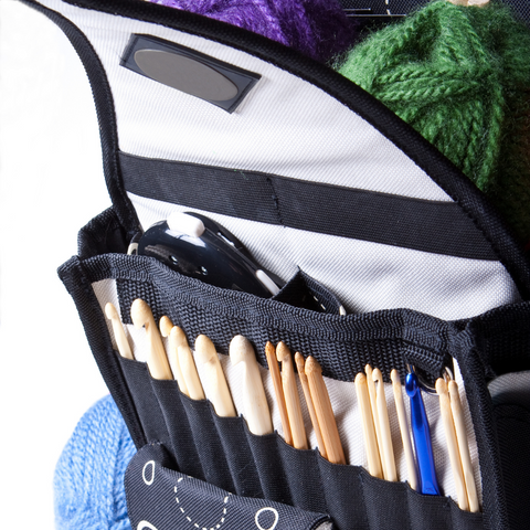 Organized crochet hooks in a case with some green, blue and purple yarns.
