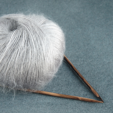 Silvery gray lace weight yarn with a fluffy halo and some wooden knitting needles.