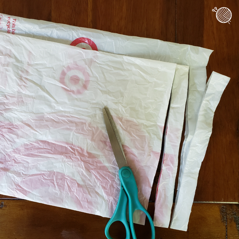 Plastic bag with two strips cut into it and a pair of scissors on a wooden table.