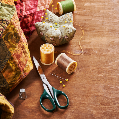 Quilting supplies including thread and scissors on a wooden table.