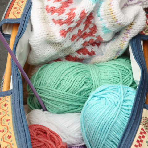 Open project bag with mint blue and green yarn and a white colorwork sweater.