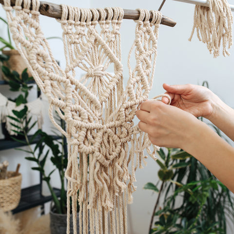 A pair of hands working on a macrame project that is hanging off a branch in front of some indoor plants.