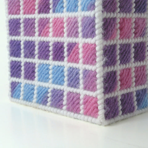The corner of a cube made from plastic canvas stitched with a grid pattern of pink, purple, blue and white yarn.