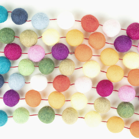 Strings of pom pom garland in a rainbow of colors.