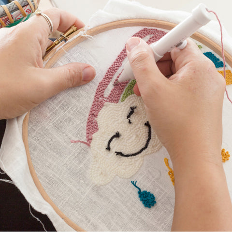 Pair of hands working a punch needle project of a happy cloud with a rainbow.