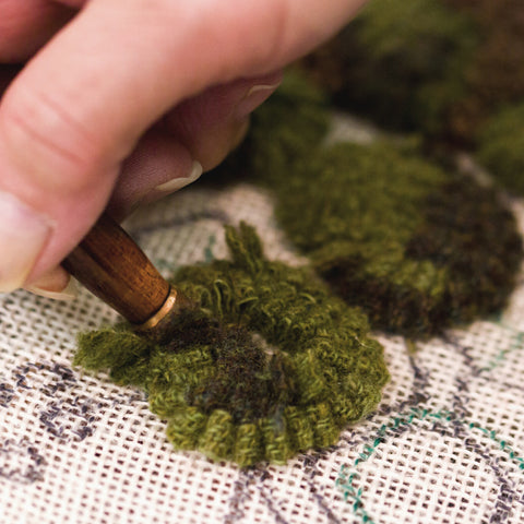 Hand working a rug hooking project with green yarn on a linen colored backing.