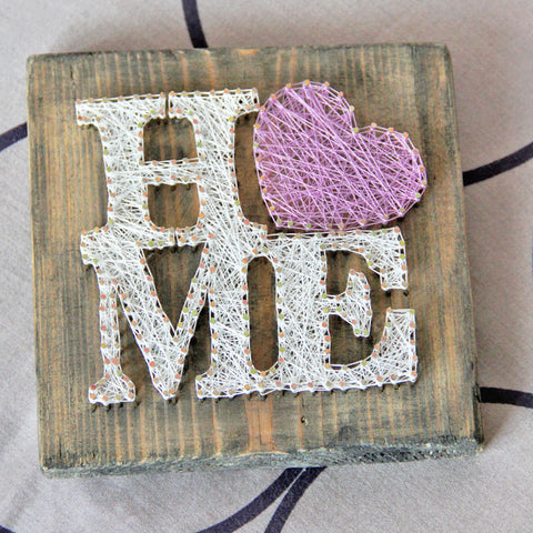 A wooden square with the word home done as a string art project where the O is a heart.