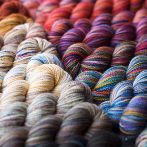A close up image of Koigu KPPPM yarns in the yellow, blue, red, purple, and brown colorways.