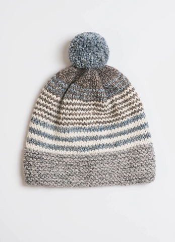 Slouch Hat with a Pom Pom made with neutral shades of blue, brown, grey and cream colored wool yarns from Blue Sky Fibers. A quick and easy knitting pattern for crafters of all levels.