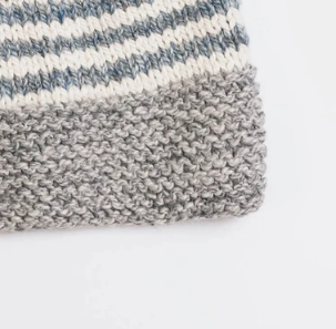 Close up image of a slouch hat with a Pom Pom made with neutral shades of blue, brown, grey and cream colored wool yarns from Blue Sky Fibers. A quick and easy knitting pattern for crafters of all levels.