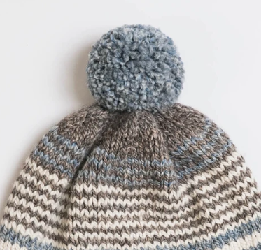 Close up image of top of a slouch hat with a Pom Pom made with neutral shades of blue, brown, grey and cream colored wool yarns from Blue Sky Fibers. A quick and easy knitting pattern for crafters of all levels.