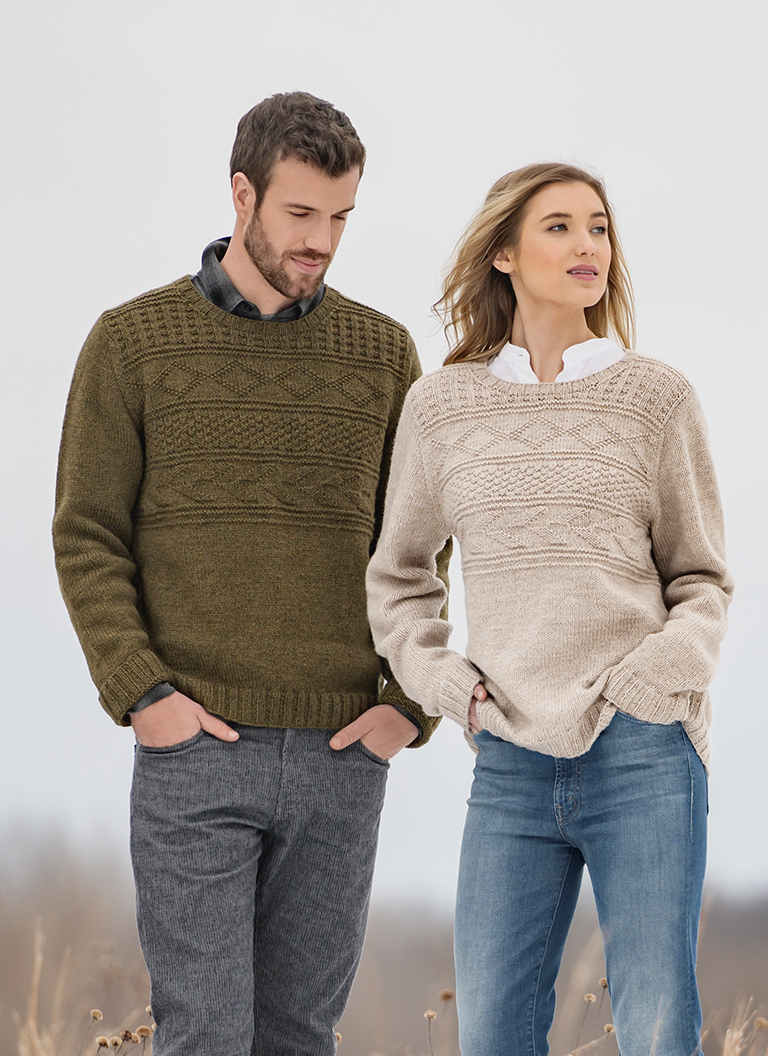 Man in Olive Pemberton Pullover standing in a field next to a young woman in a tan colored, knitted pullover made with Blue Sky Fibers Woolstok yarn.