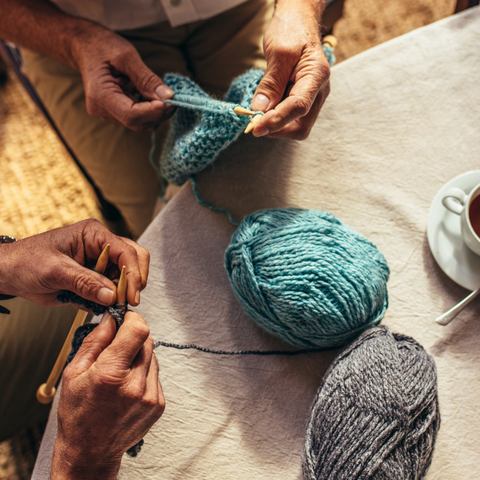 Overhead image of hands knitting with balls of yarn on a table.