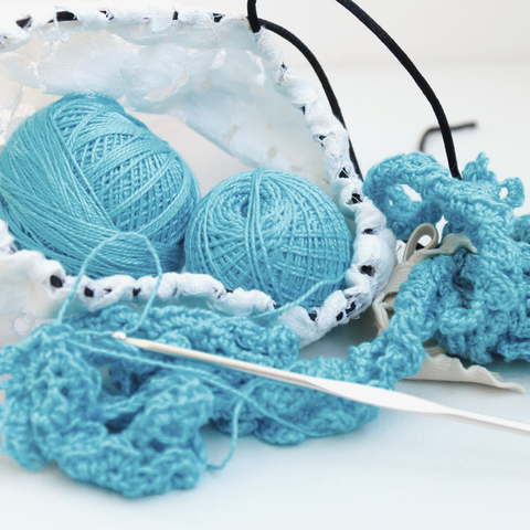 Two balls of light blue yarn being crocheted into lace.