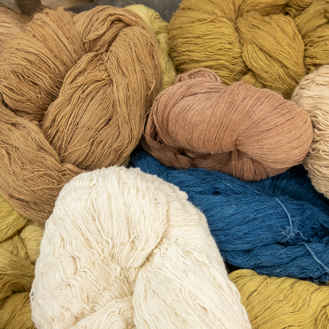 Skeins of yarn in natural shades of tan, yellow, peach and blue.