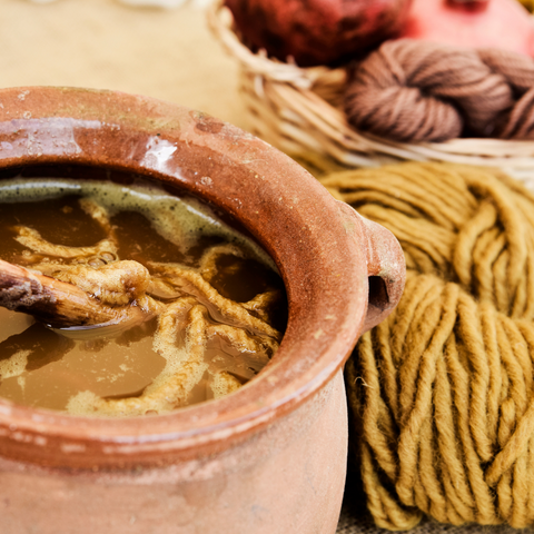 Terra cotta pot with a skein of yarn being dyed a golden color with other skeins of yarn in rusts and gold in the background.
