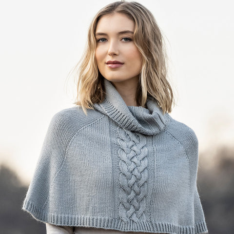 young woman wearing a blue poncho made from wool yarn.