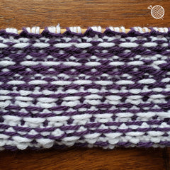 Wrong side of a piece of colorwork knitting in purple and white.