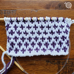 Piece of colorwork knitting in white and dark purple with small pattern.