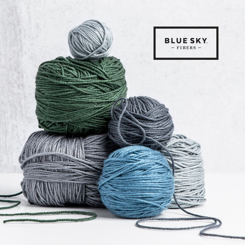 four balls of yarn in green, blue, and grey shades stacked on top of one another.