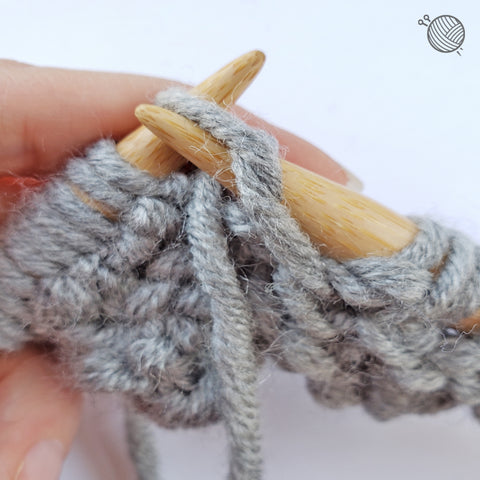 Step 7 of Star Stitch Tutorial: To finish Row 2, repeat the p1, [p3tog, yo, p3tog] to the last stitch which is a p1.