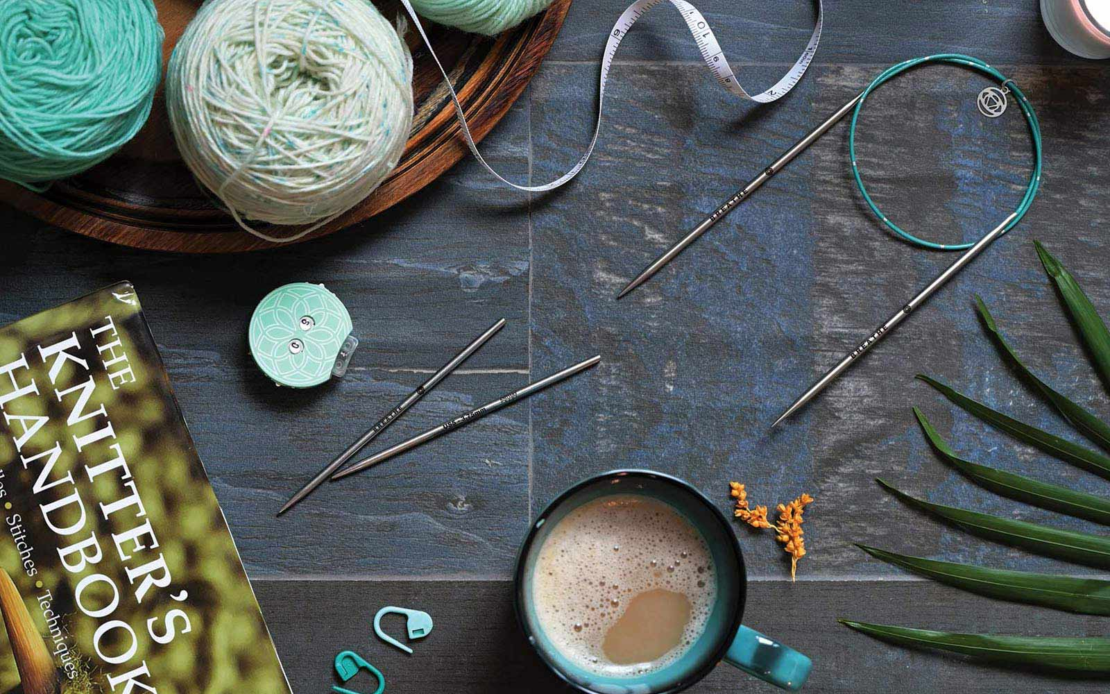 Mindful interchangeable knitting needles, Stitch Markers, tape measure and Knitter's Handbook from Knitter's Pride Mindful Collection displayed with a cup of coffee and teal balls of yarn.