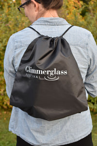 Black bag with the words Glimmerglass Festival logo imprinted in white. The bag is opened and closed using strings at the top. It can be worn as a backpack over both shoulders.