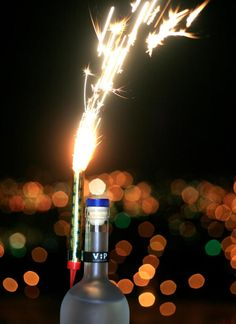 sparkling candle on a champagne bottle