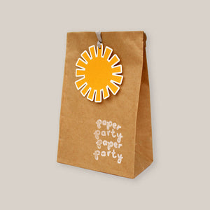 A paper party bag with sunshine tag and hand printed motif - set of 5