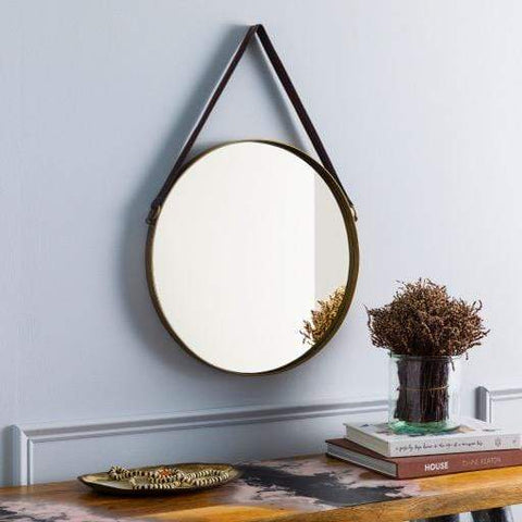 Fennex Mirror features a brown leather strap with a brass circular mirror for sustainable furniture modern style front view