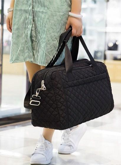 Casual Stylish Woman With Black Quilted Travel Bag - Side View