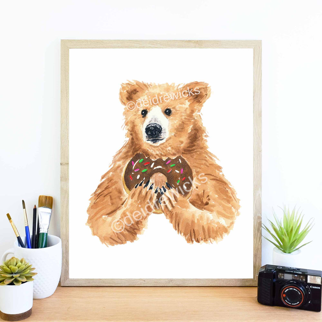 Watercolor print of a brown bear eating a donut by Deidre Wicks
