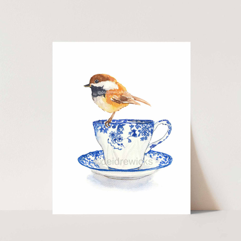 Watercolor of a chestnut backed chickadee sitting on a blue flowered vintage teacup