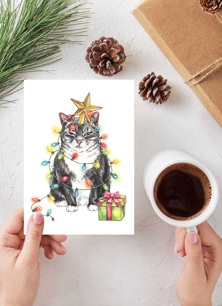 Christmas card featuring a grumpy tuxedo cat dressed like a Christmas tree