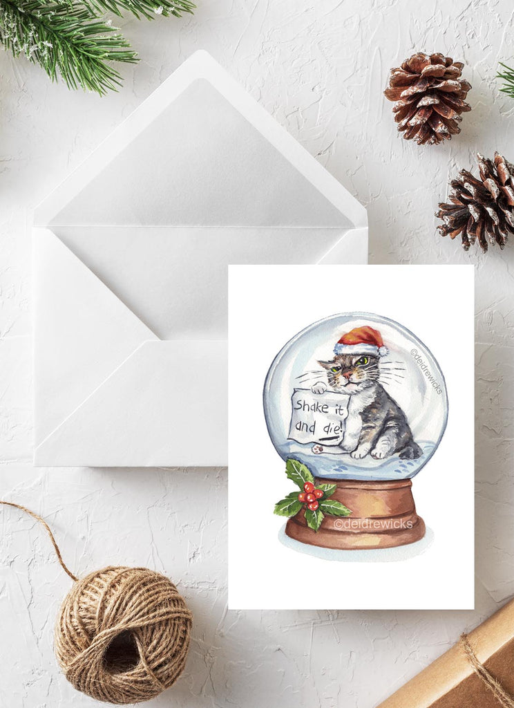 Christmas card with an angry tabby cat inside a snow dome holding a warning sign not to shake it