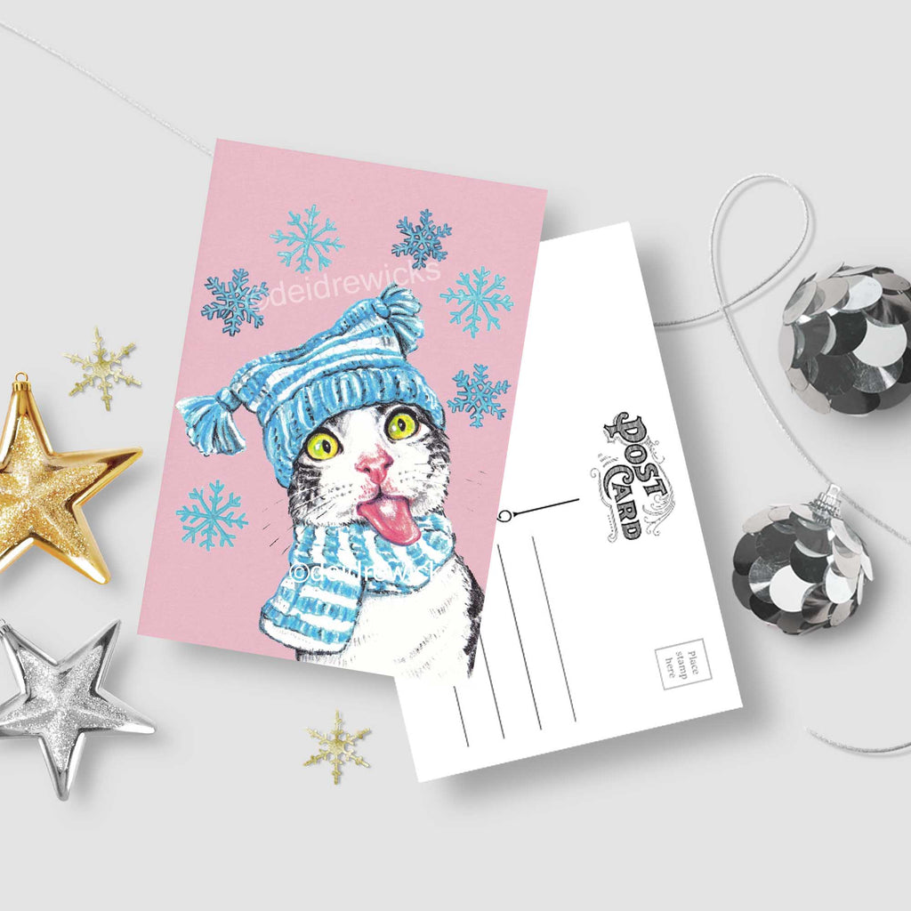 Christmas cat postcard - Crayon drawing of a grey tabby sticking out her tongue to catch snowflakes