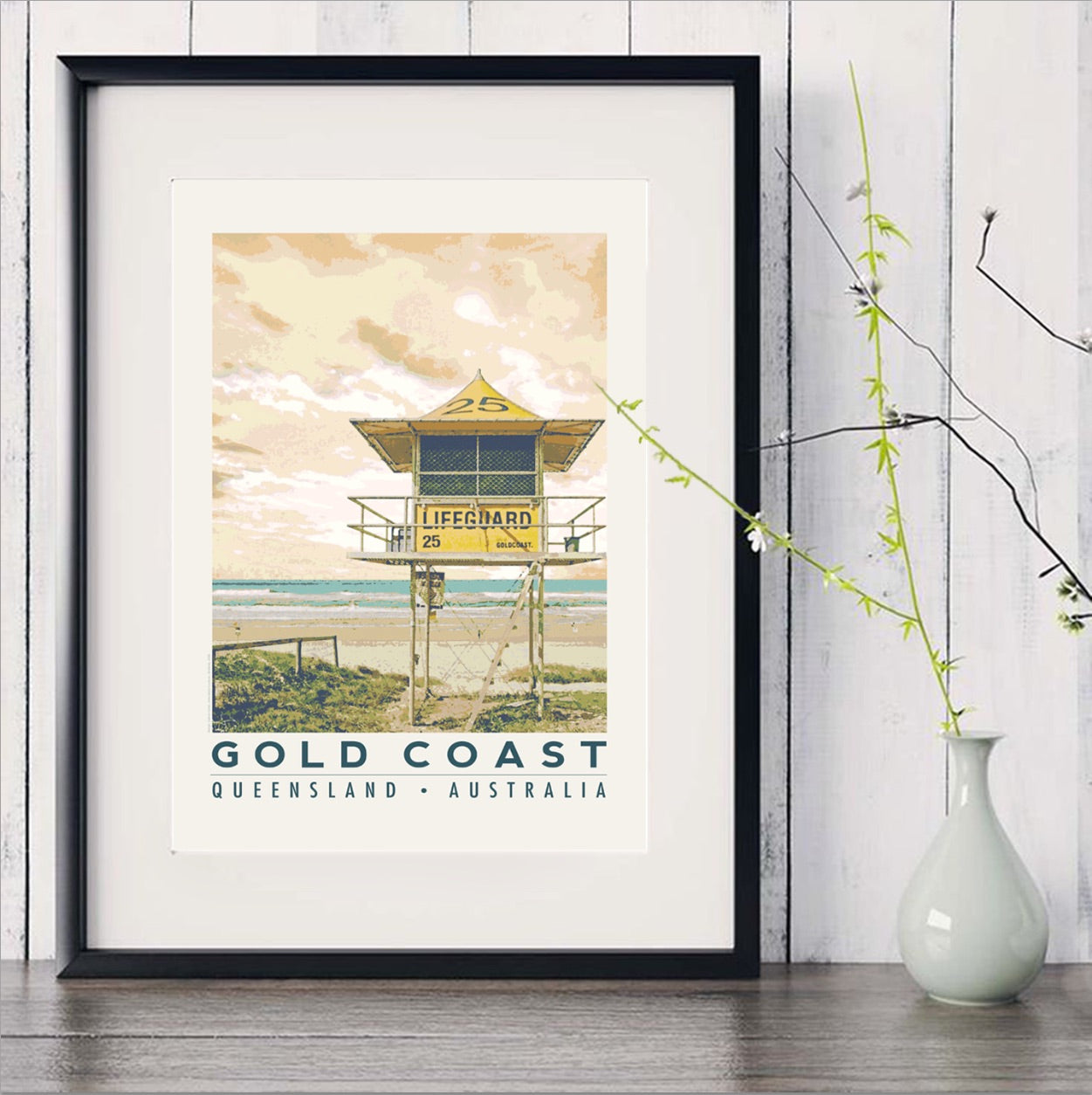 Gold Coast beach with lifeguard tower art print in black frame with white vase