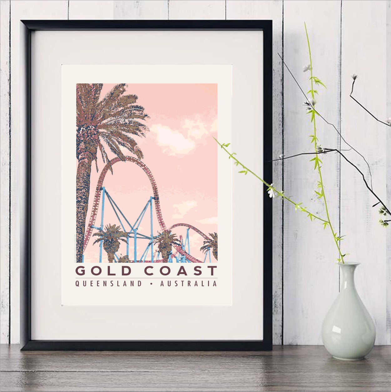 Gold Coast poster roller coaster with palm in black frame with white vase