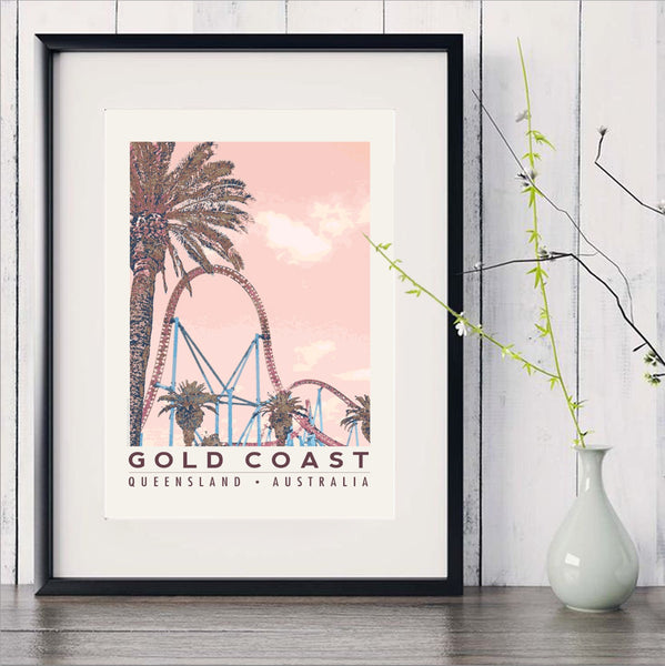 Gold Coast roller coaster with palms art print in black frame with white vase