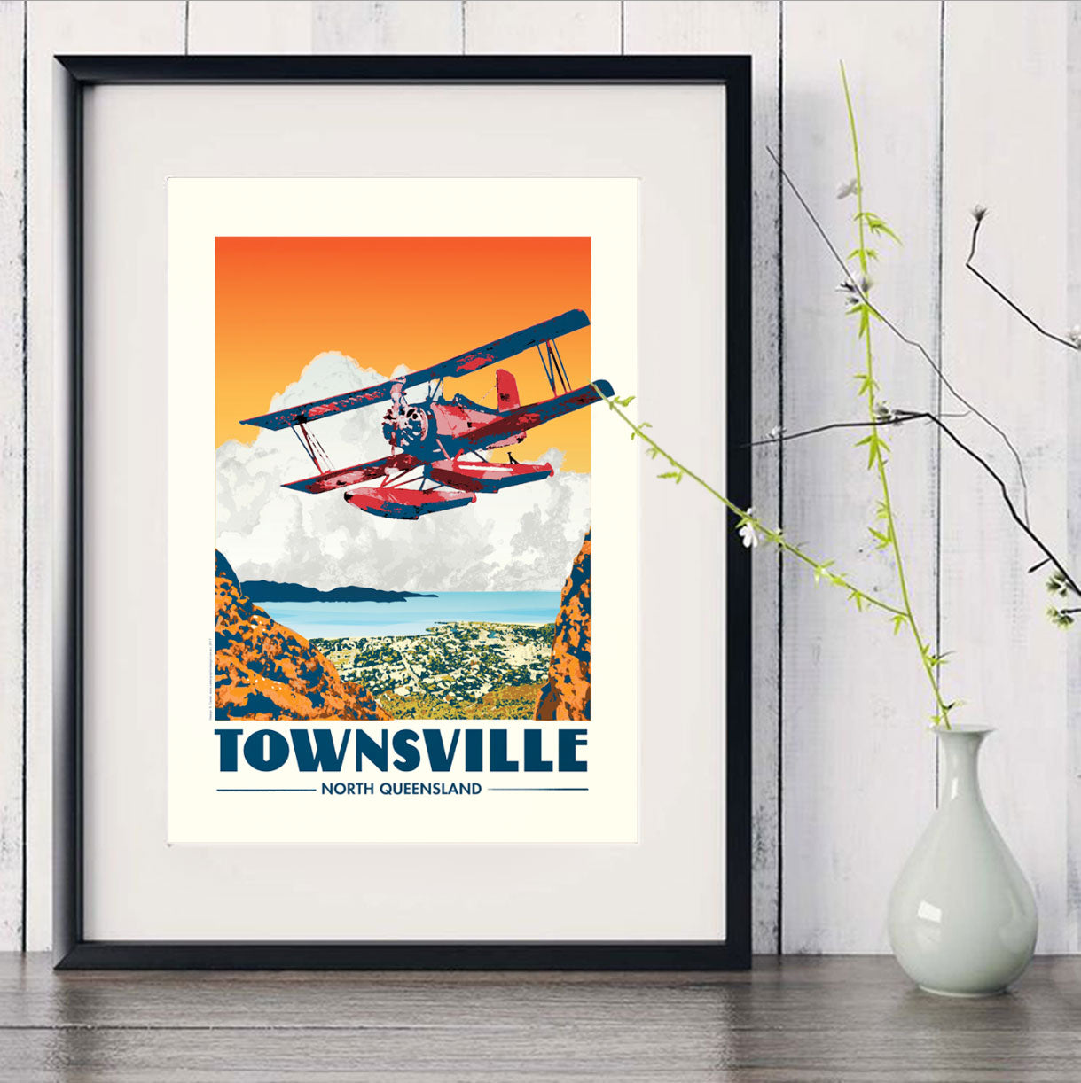 Townsville Red Baron flying over Castle Hill art print in black frame with white vase
