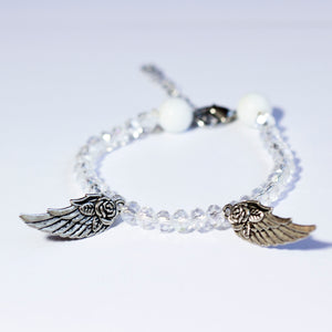 White beaded bracelet made of crystal beads featuring metallic angel wing pendants and a chain clasp design