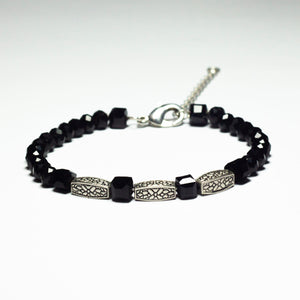 Black beaded bracelet made of crystal beads featuring metallic engraved brick pendants and a chain clasp design
