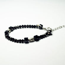 Load image into Gallery viewer, Black beaded bracelet made of black crystal beads featuring engraved cylinder pendants and a chain clasp design