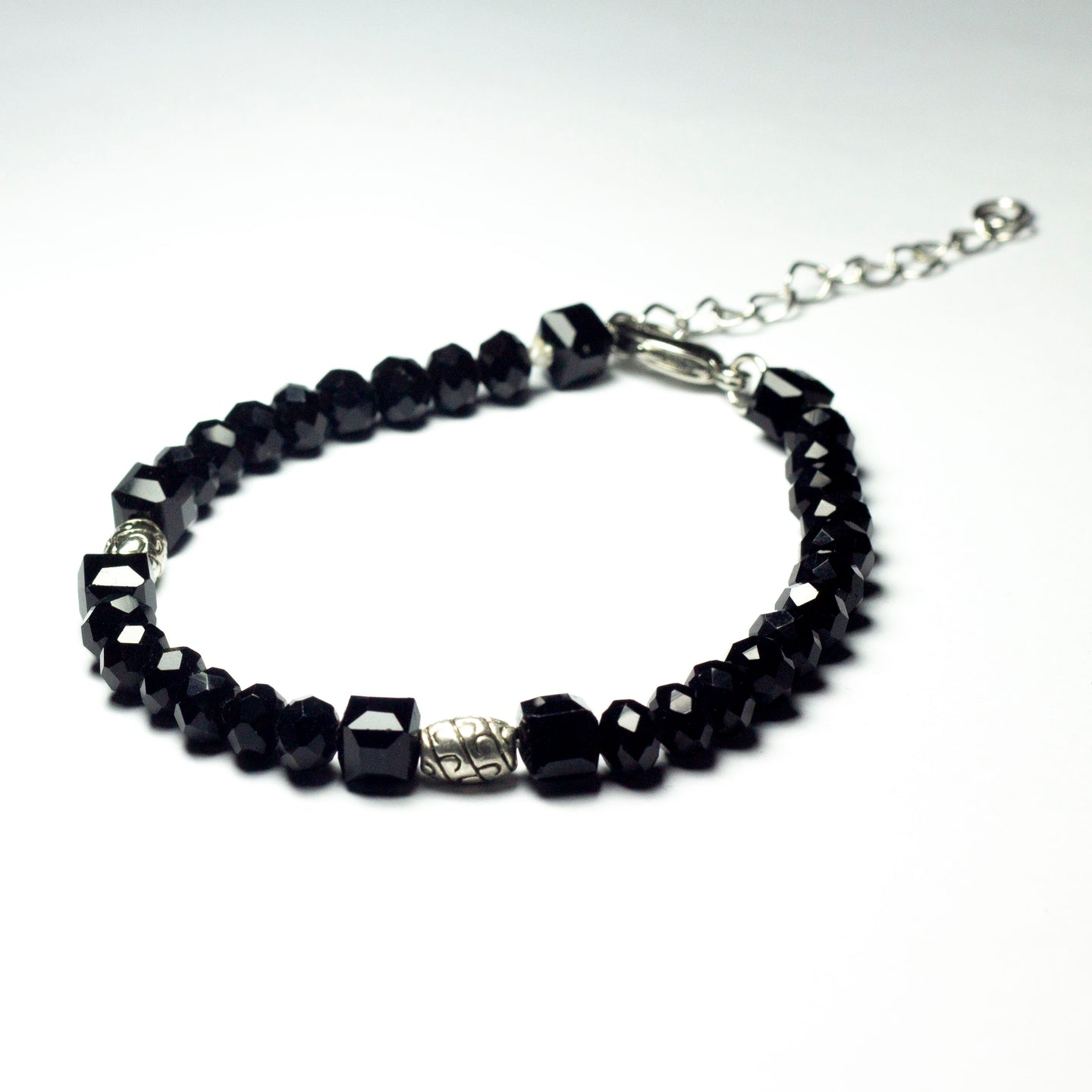 Black beaded bracelet made of black crystal beads featuring engraved cylinder pendants and a chain clasp design