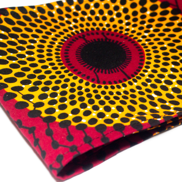 African print head wrap in a red, yellow and black polka dot print