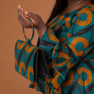 Leather bag with ring shaped handle, velvet lined interior and a geometic orange and green African Print overlay