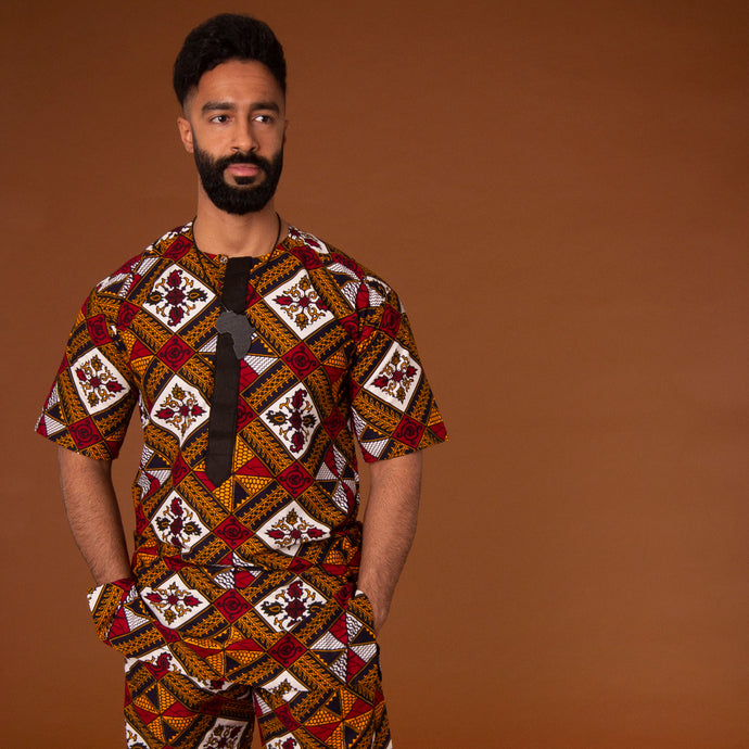 African print kaftan top with black crepe trim on the neckline hand-made from red, yellow, white and black ankara wax print in a geometric pattern