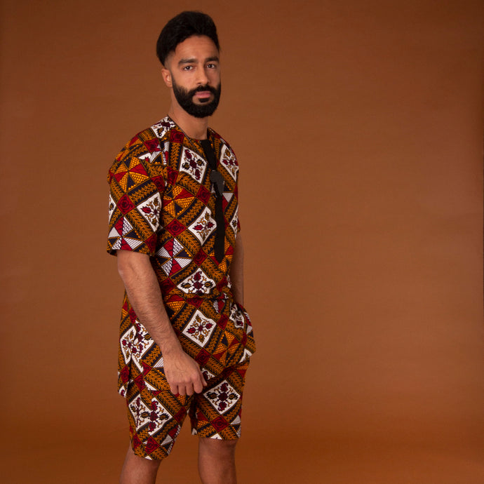 African print kaftan top with black crepe trim and matching shorts with drawstring waist hand-made from red, yellow, white and black ankara wax print in a geometric pattern