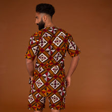 Load image into Gallery viewer, African print kaftan top with black crepe trim and matching shorts with drawstring waist hand-made from red, yellow, white and black ankara wax print in a geometric pattern